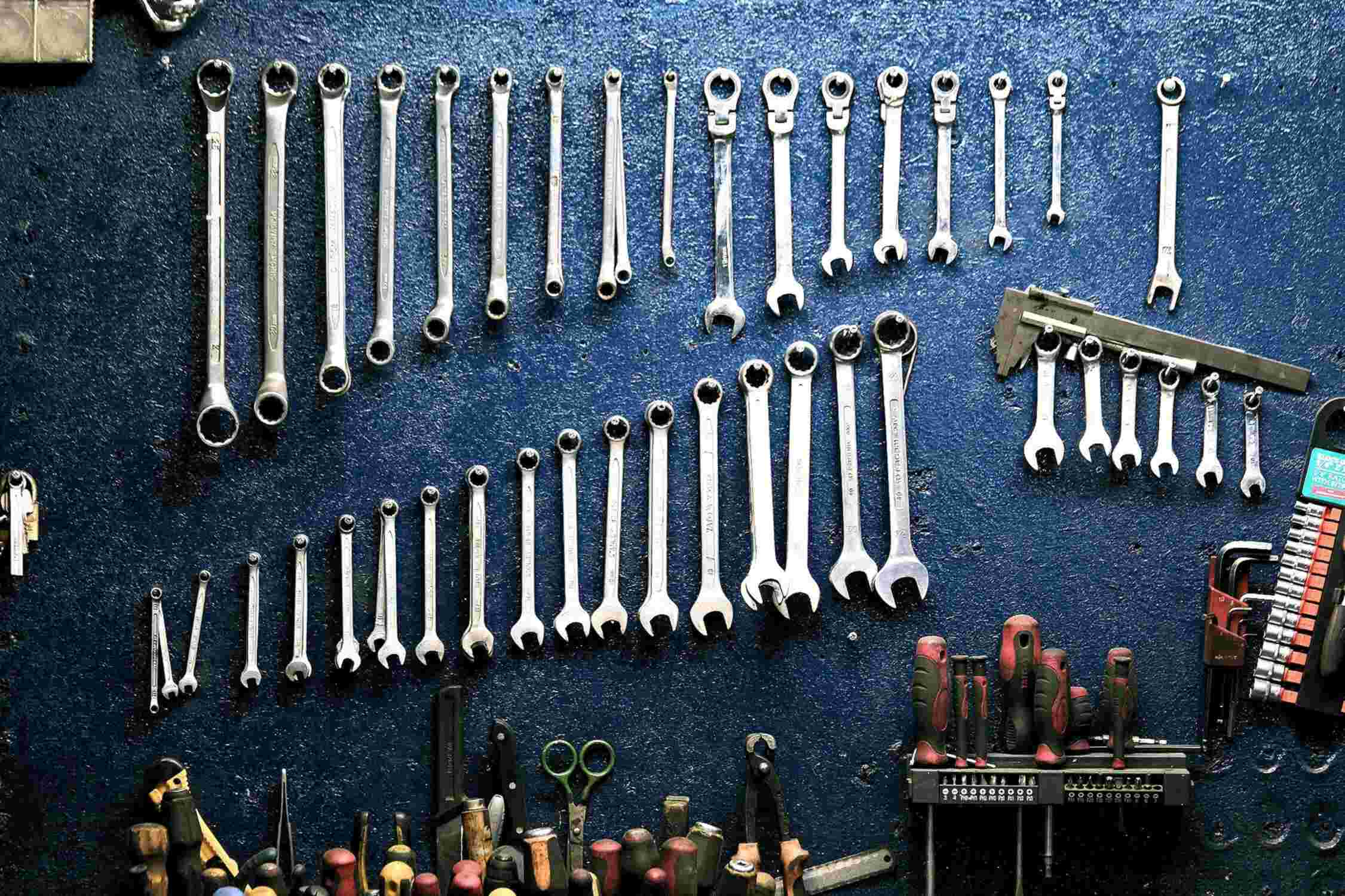 Wrenches of various sizes on blue wall