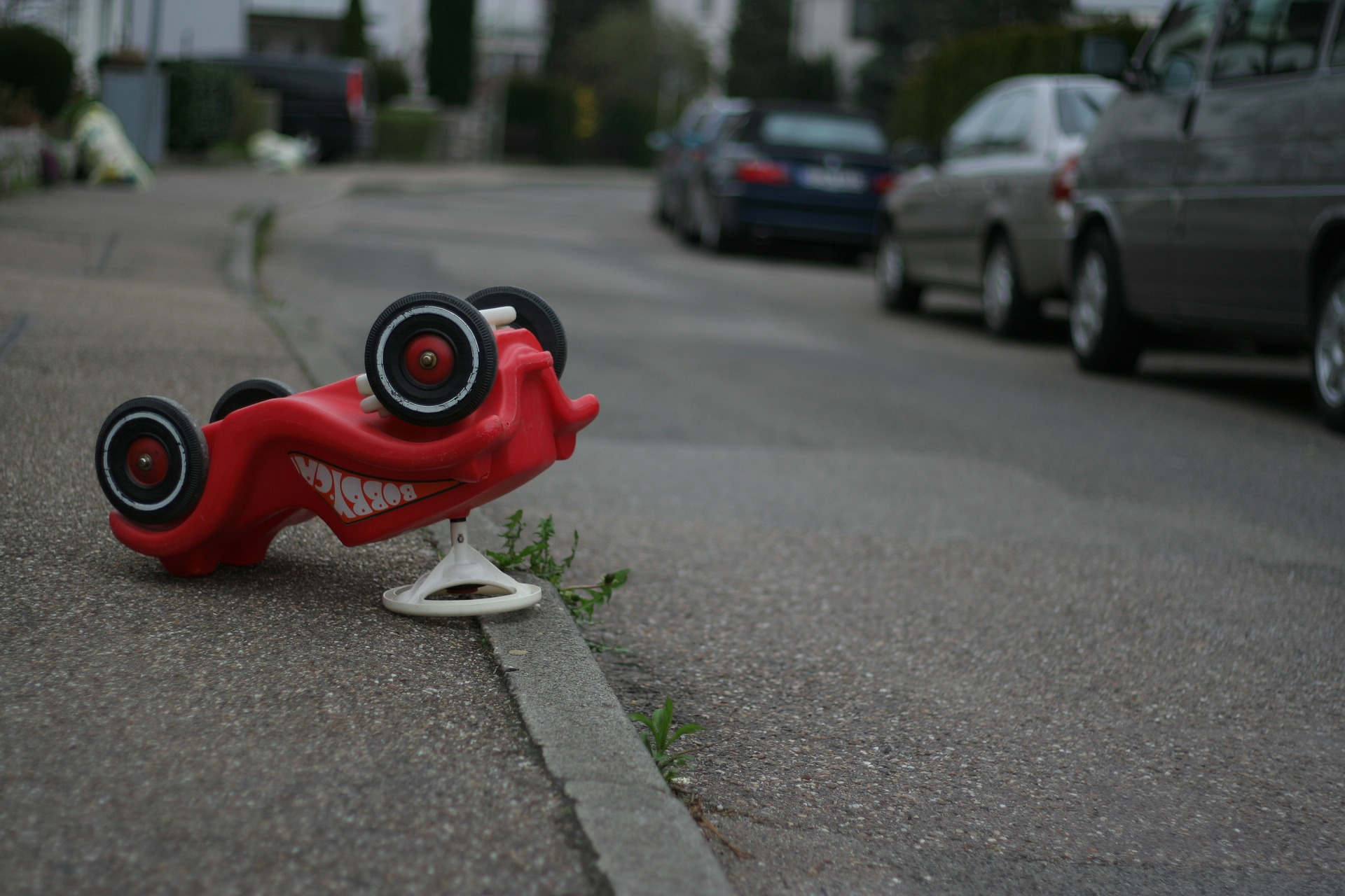 Red toy car flipped on curb